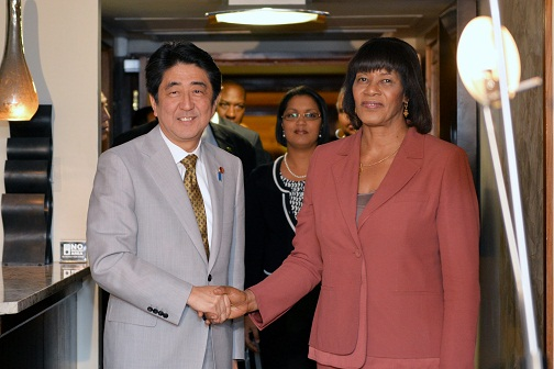 Jamaica's Prime Minister Portia Simpson Miller (right), greets  the Prime Minister  of Japan, Shinzo Abe (left)
